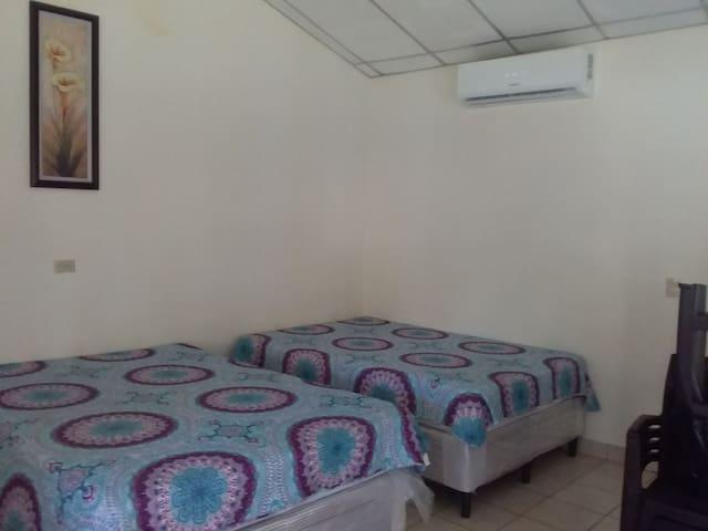 Habitacion con aire acondicionado y 3 camas.  Room with A/C and three beds.