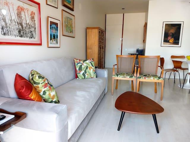 Sala com sofá cama e poltronas. Armário com a louça e mesa para refeições.