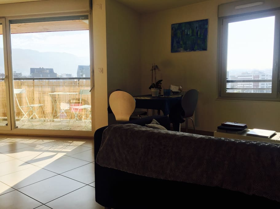 Salon avec accès sur le balcon: baie vitrée donnant la vue sur les montagnes ( tournette, semnoz)