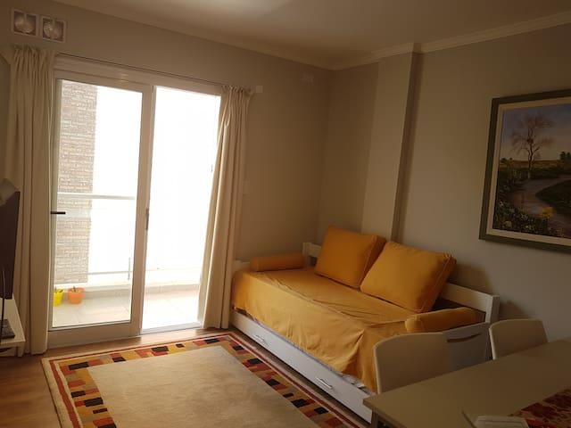 """Living y balcón con mucha iluminación y ventilación. Smart TV 32""""."""