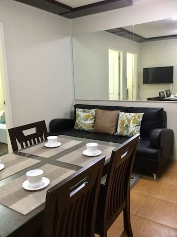 The dining area facing the living room with soft & comfly black sofa for your relaxing time :)