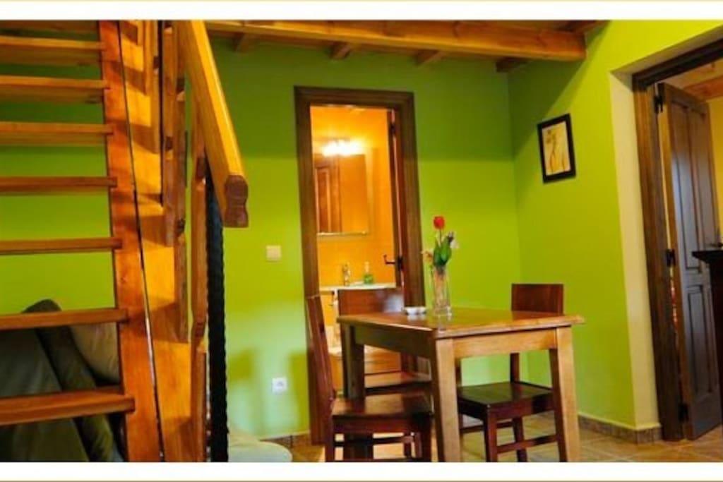 foto tomada desde la puerta de la cocina , escalera ahacia habitacion de arriba y a la derecha puerta a habitacion principal al lado de la chimenea , al fondo el baño