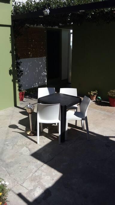Patio equipado con mesa de jardin y cuatro sillas. excelente para tomar mates a la tarde.