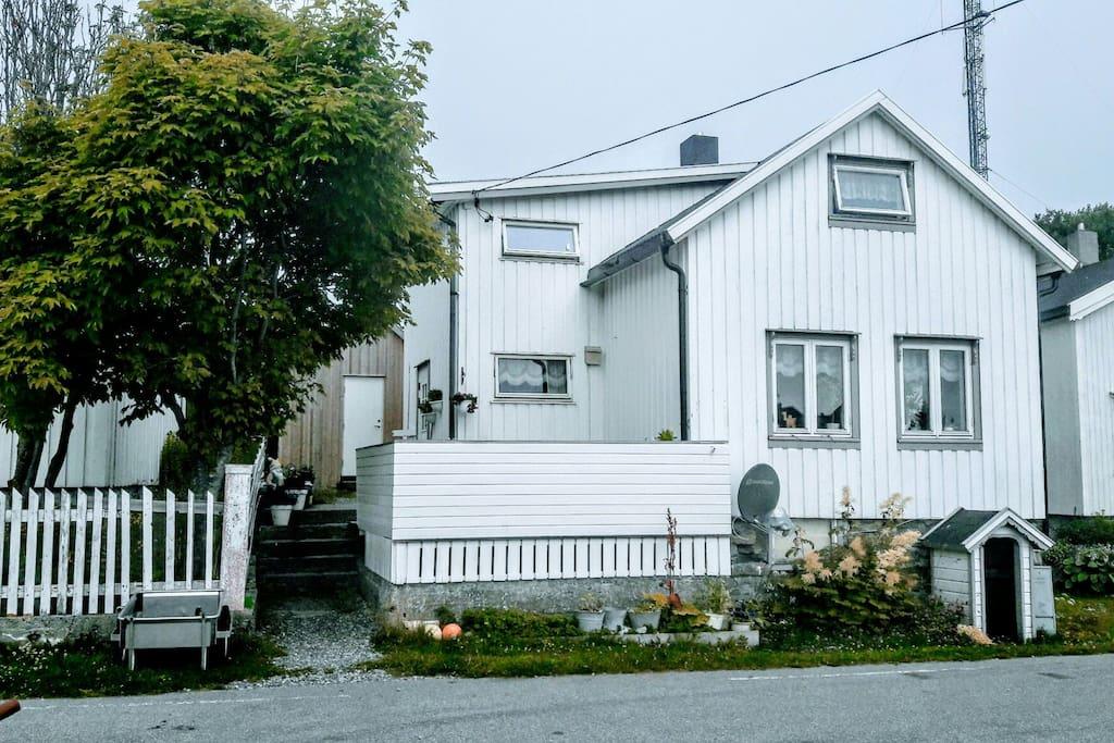 Huset sett fra veien. Anneks i bakgrunn. Veranda 1 mot veien og sjøen. Hage bak huset.