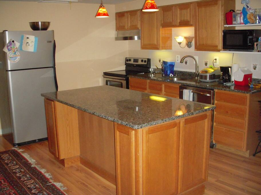 full kitchen with granite counter top and full dinnerware sets