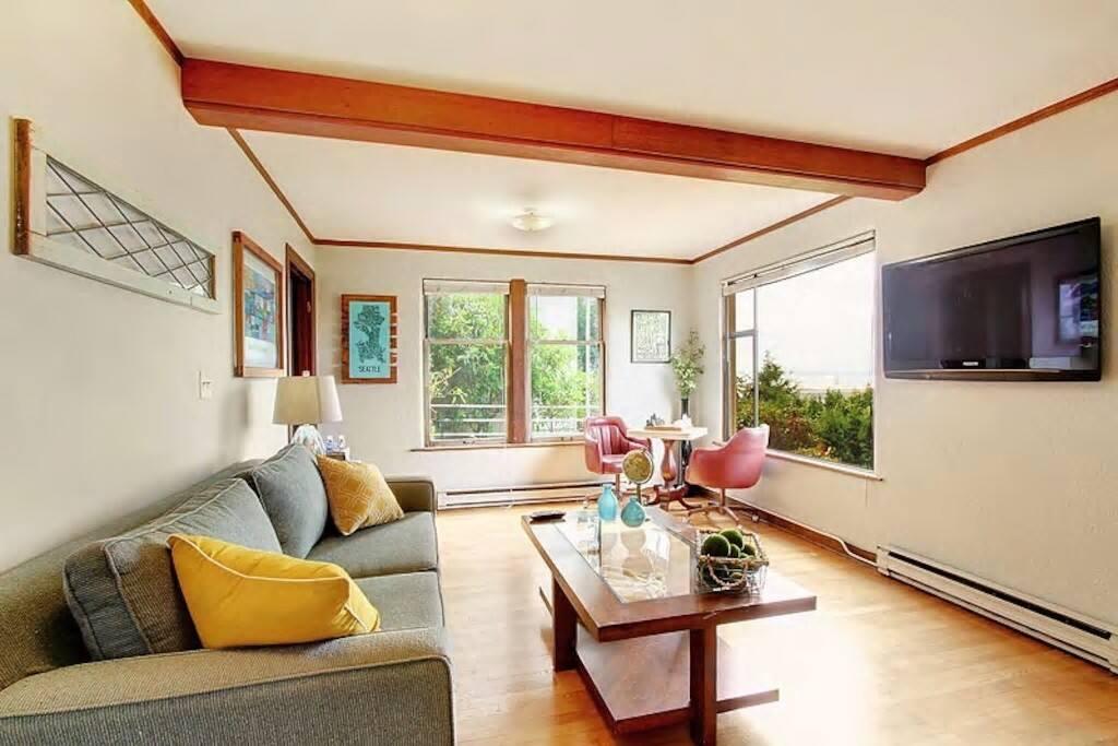 Large view living room w/ hardwoods, mahogany trim, built-in, fun artwork & furnishings!