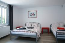 Sleeping room with big bed for two people and one bed for one person