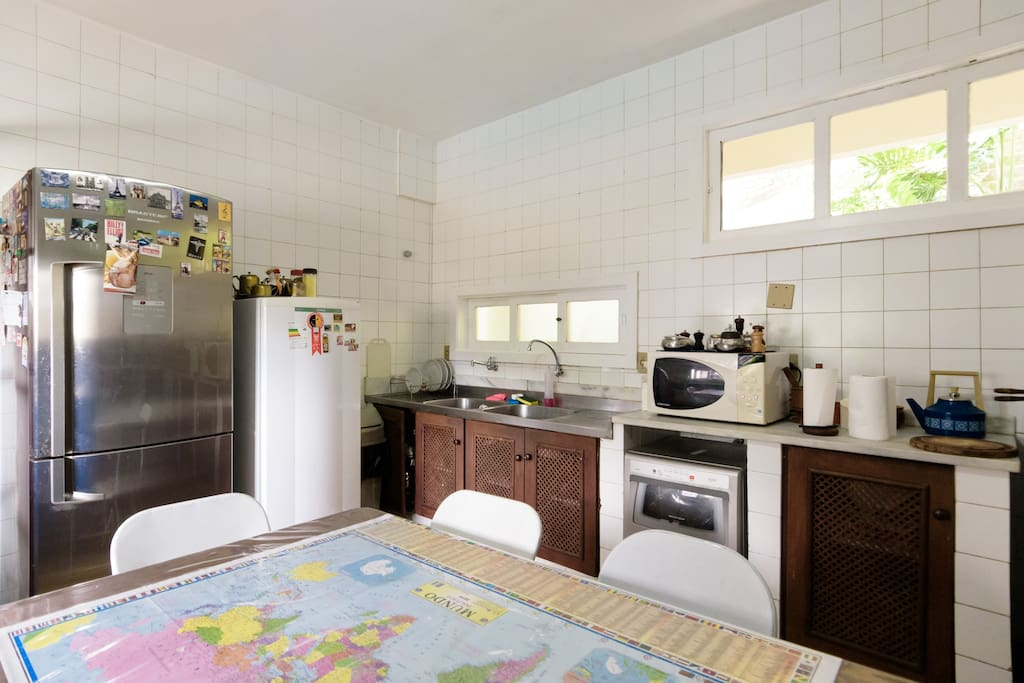 Cozinha, equipada com geladeira branca, apenas pros hospedes, microondas e duas pias.