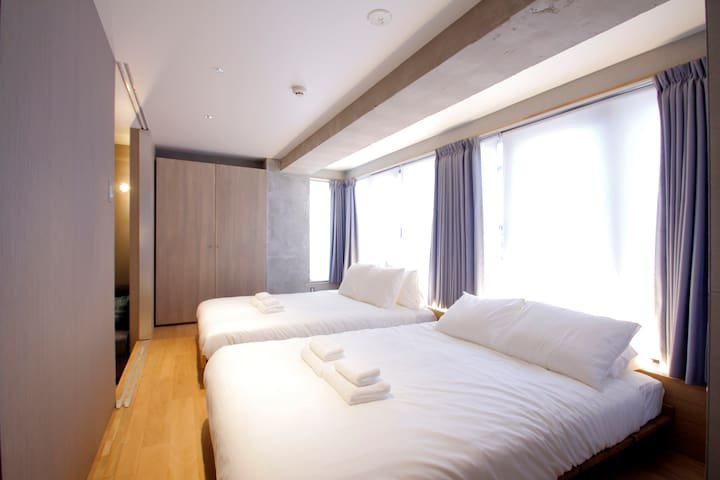 Two double beds are in the bedroom. They are on a slightly elevated platform in the room.