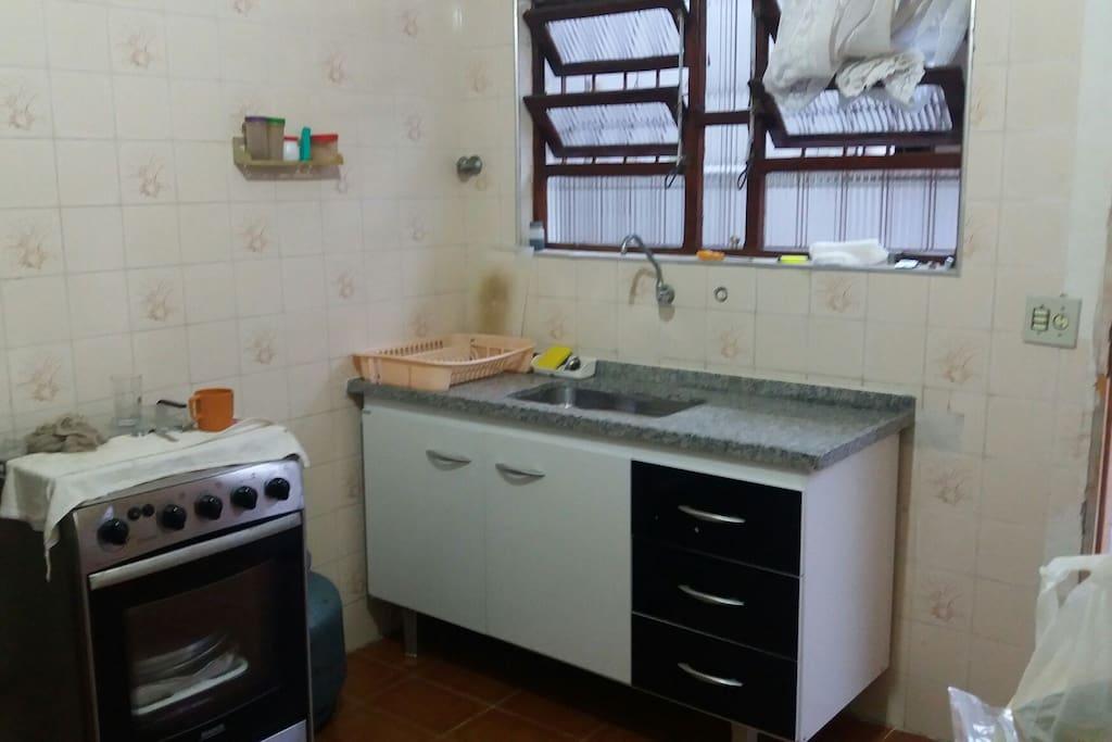 Cozinha equipada com micro-ondas, panela elétrica, fogão,  geladeira, utensílios e ventilador de teto.