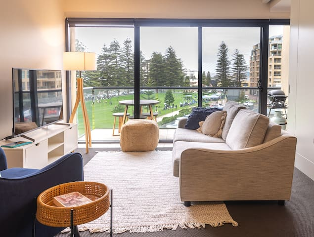 Living and dining room overlooking Colley Reserve with balcony including Weber gas BBQ and outdoor setting.
