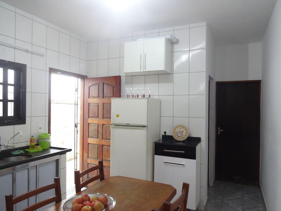 Cozinha completa e equipada com fogão e forno, microondas, geladeira, pia, armários, utensílios de cozinha e mesa com 6 cadeiras.