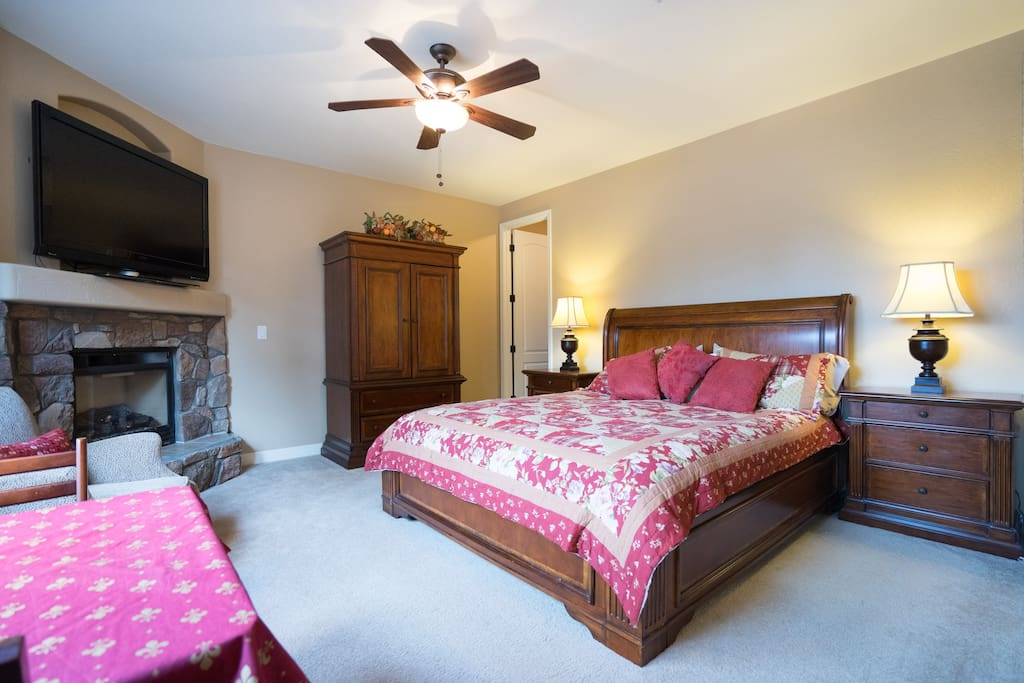King bed, closet, table, TV and fireplace