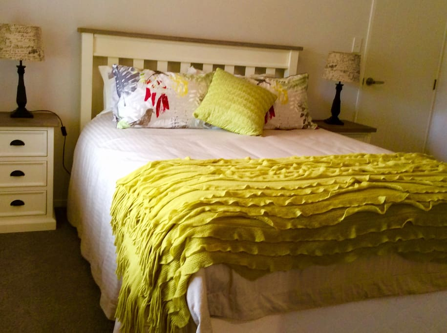 Main bedroom with comfy queen bed, chest of drawers and closet.