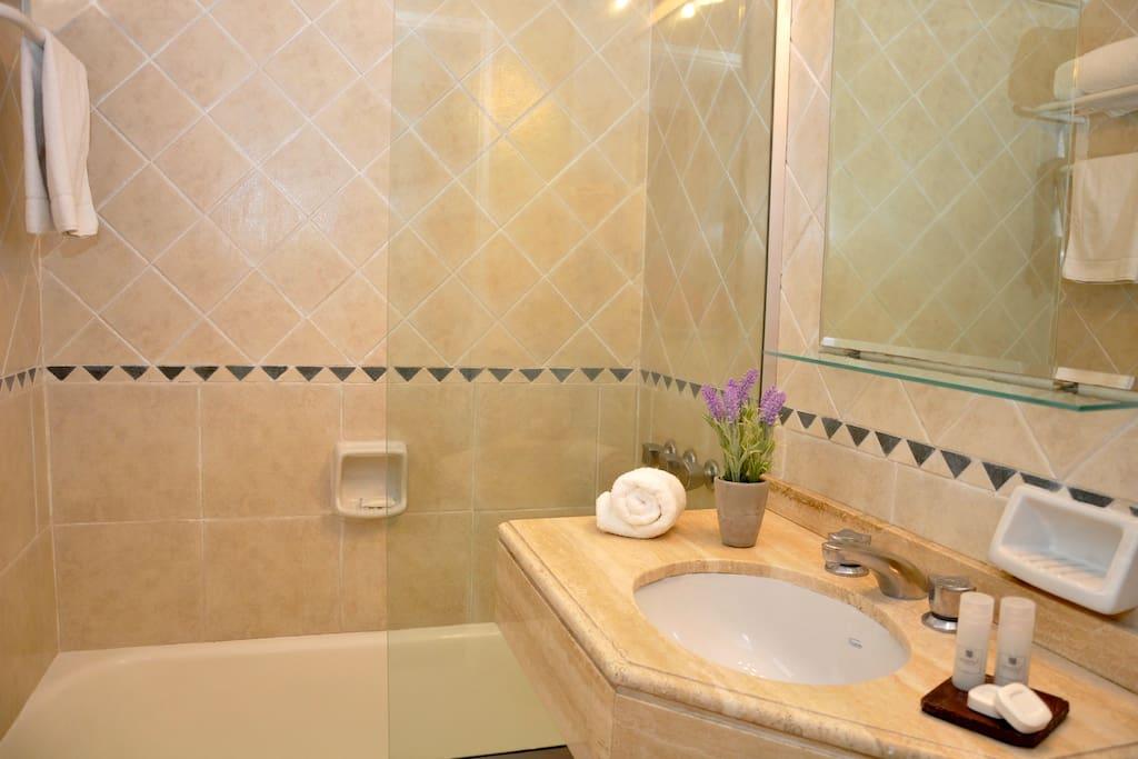 Bañadera con mampara de vidrio, secador de cabello y amenities