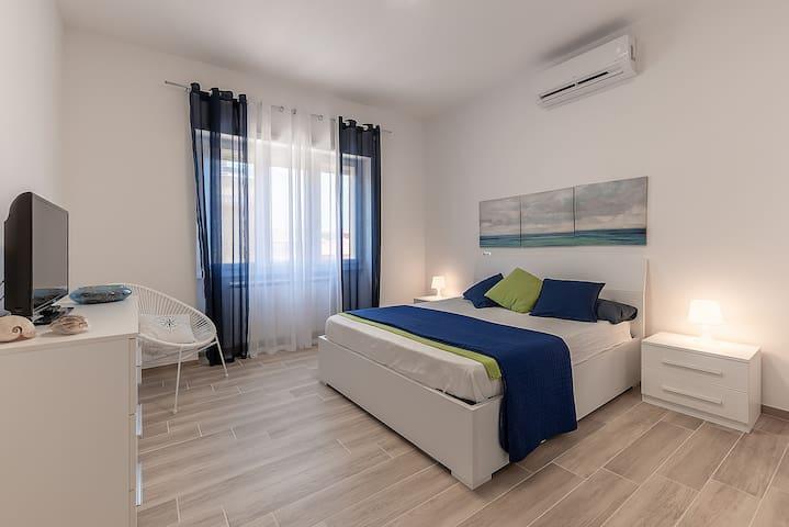 """camera da letto 1: camera molto ampia con  un letto matrimoniale contenitore, un armadio, un comò, una comoda sedia, una tv da 32"""", plafoniera con switch (luce intensa/soffusa), climatizzatore da 12000 btu"""