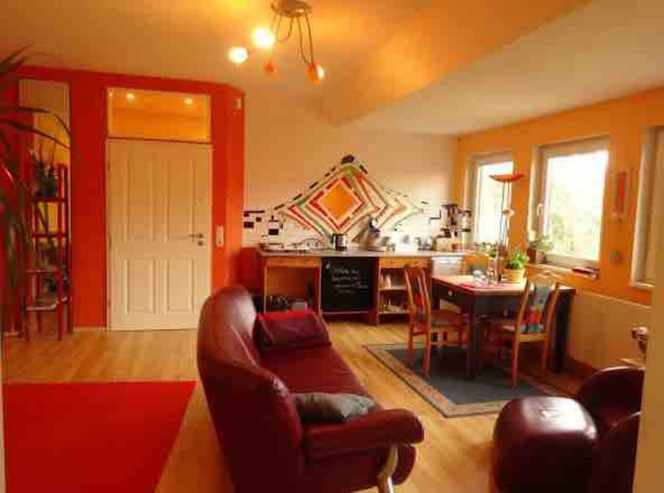 Gemütlicher Gemeinschaftsraum mit Miniküche, Esstisch, Sofa, TV. Von diesem großzügigen sehr hellem Zimmer gehen die 3 Schlafzimmer und das Bad ab.