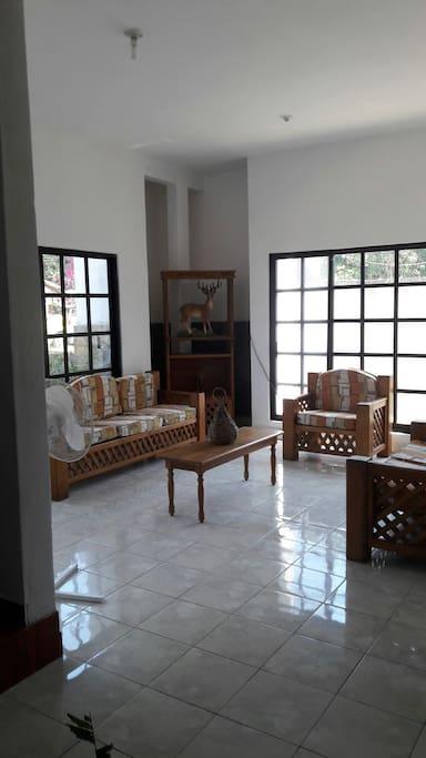 amplia sala rustica con vista a las jardineras de la casa.