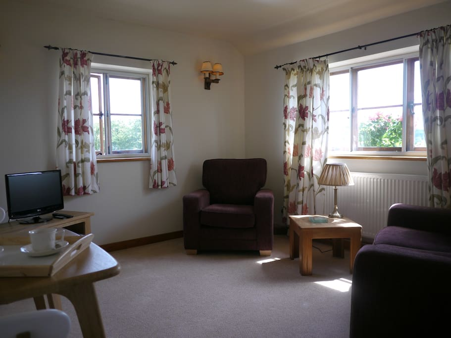 Light spacious lounge  with comfortable seating and dining area for 2 with views towards the Malvern Hills