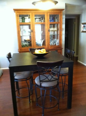 Pub height table and side armoire filled with glassware and servingware for entertaining.