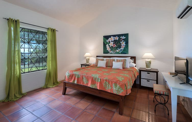 The master bedroom with a king bed, air-conditioning, TV, ocean views and en suite bathroom