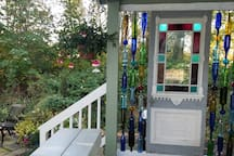Antique door and colored bottles add to the charm of the covered porch.