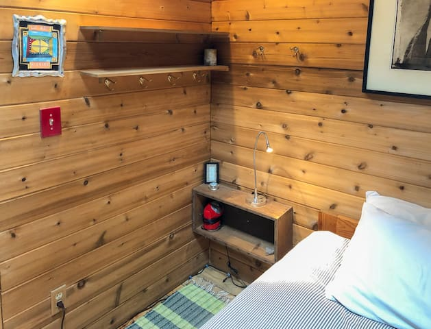 Bedroom with solid cedar walls and pine floors, skylight overhead. Organic cotton bedding and down comforter to stay cozy. Plenty of extra blankets available.