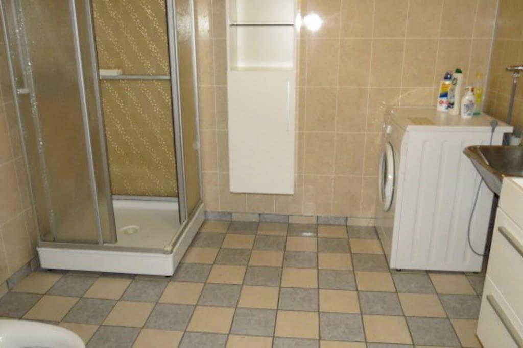 Baderom med baderomsinnredning, dusjkabinett og klosett samt vaskerom.