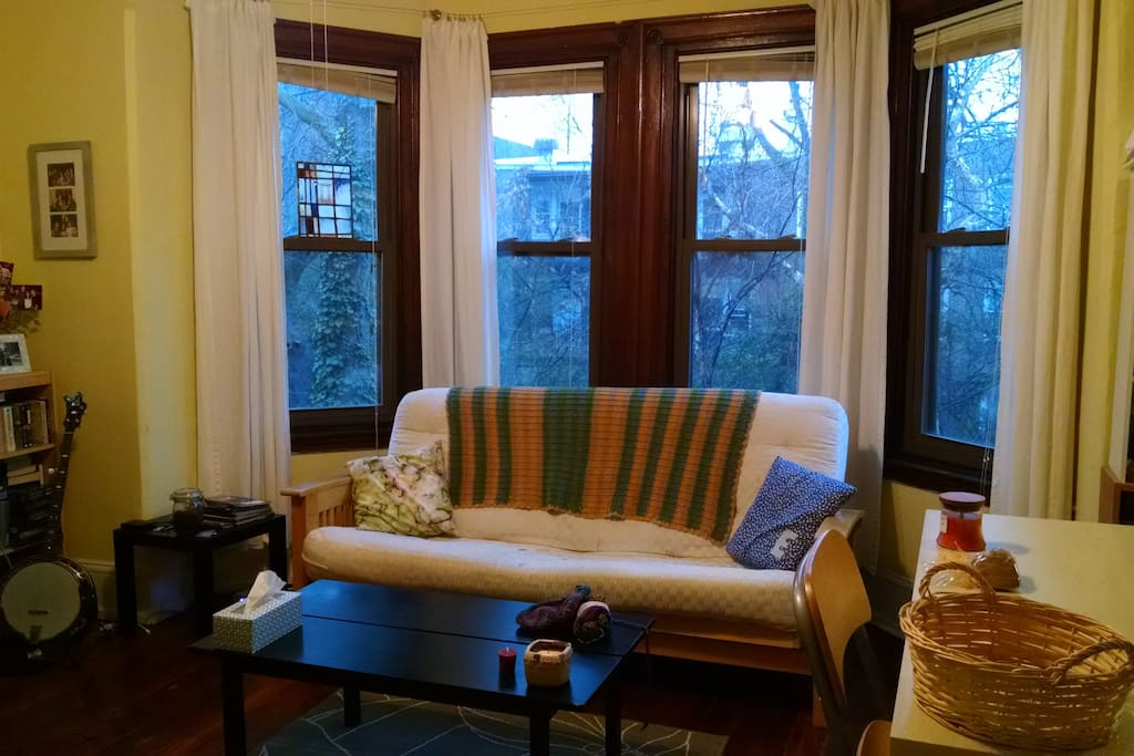 The living room has beautiful bay windows.  The futon can be folded out to sleep up to 2 more people.