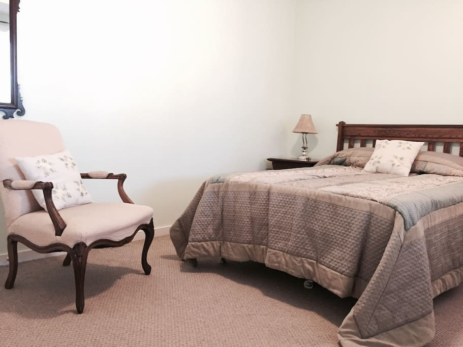 Spacious bedroom with double bed, large closet, dresser and night stand.