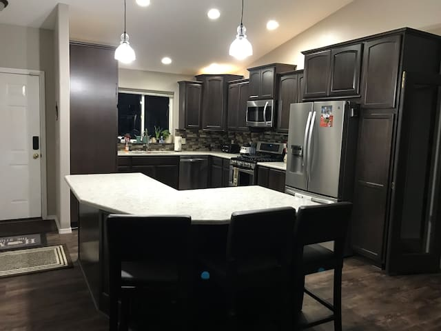 Newly renovated kitchen with gas range, microwave, dishwasher & fridge. Seating for 5 at the large island.