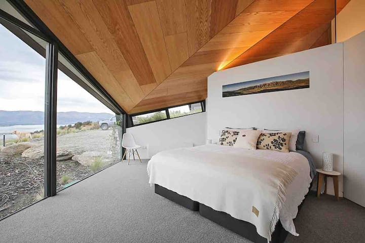 The master bedroom is oriented to take in the Clutha River and the St Bathans mountain range.