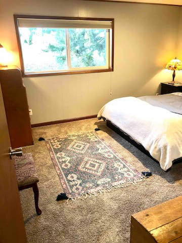 Bedroom with a queen size bed and extra pillows. Dresser,  full size closet and full length mirror and alarm clock to help you feel at home. Blackout blinds for when you want to sleep in.