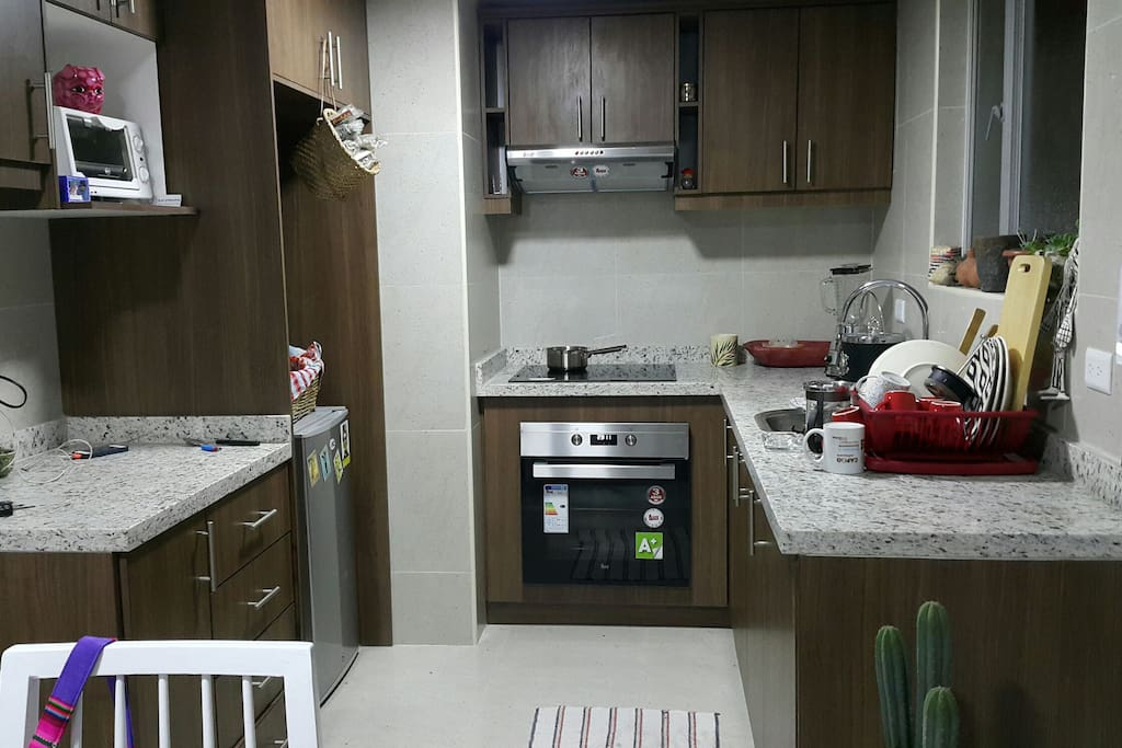 kitchen with electirc stove and oven, electric kettle, blender, french coffee maker.
