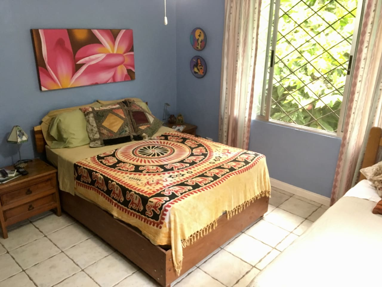 Double bed in a bright  room. Eclectic decor.