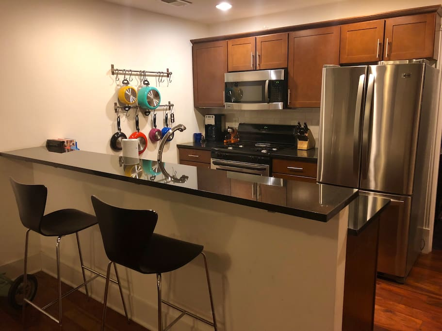 Fully equipped kitchen with bar, granite counters, stainless  steel appliances, and gas range