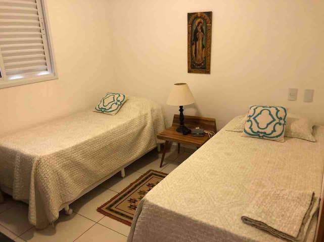 Quarto com 2 camas de solteiro e 1 colchão extra