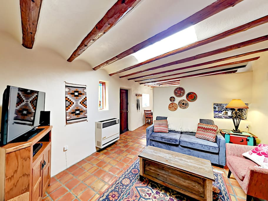 Southwestern charm is on full display with a kiva fireplace, stained glass windows, and vigas ceiling beams.