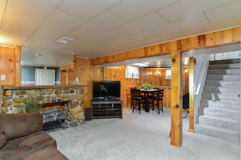 Basement family room with sectional, fireplace, TV, dining table