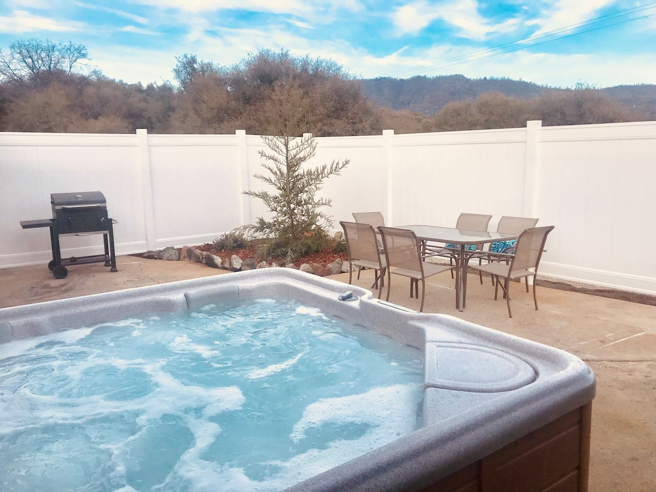 Private hot tub and patio with mountain views and BBQ.
