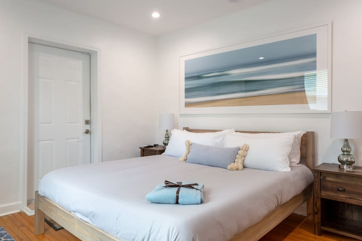 Our master bedroom features a cali king size bed and two nightstands with an Alexa on the right nightstand.