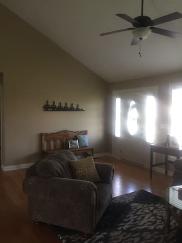 The living area has a cushy couch and oversized chair.  It is open to the dining/kitchen.