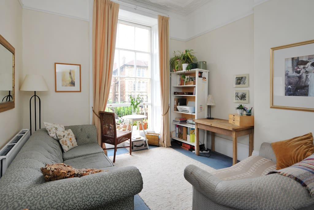 Sunny lounge with floor to ceiling sash window.