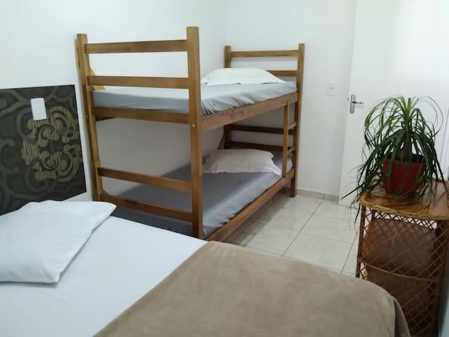 Quarto com cama de casal e uma beliche e ar condicionado. Observação: Não fornecemos roupas de cama e banho.