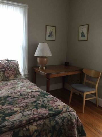 The small bedroom has a single bed and nice table with lamp and chair.  There are two windows for wonderful light and a generous closet.