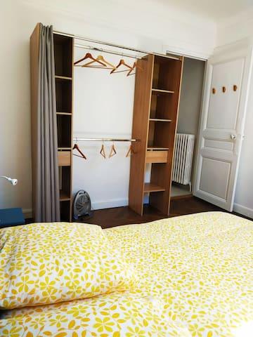 Chambre avec armoire, porte donnant sur la salle de bains