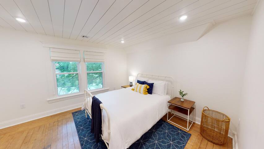 The second bedroom has a queen bed and blackout window treatments.