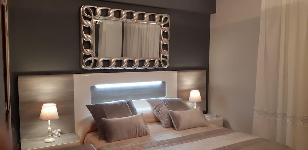 Detalle del cabecero de la cama con luz LED y lámparas en cada mesita