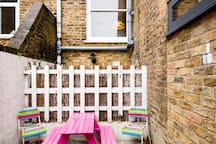 Internal courtyard accessible via the kitchen. Children's picnic table and outdoor toys.
