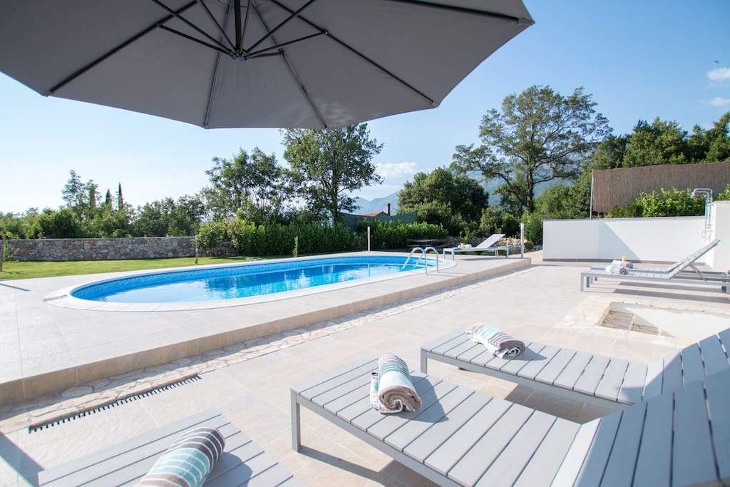 Beautiful swimming pool area, fully equipped with sunbeds, parasols and showers. Pool is surrounded with lawn.